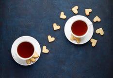Thé romantique pour des amants le jour de valentines L'amoureux a formé des biscuits avec deux tasses de thé sur le fond en pierr images libres de droits