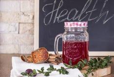 Thé rouge avec de la cannelle et des herbes sur le fond de panneau de craie Photos stock