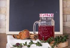 Thé rouge avec de la cannelle sur le fond de panneau de craie Images libres de droits