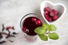 Thé rouge de ketmie dans une belle tasse, framboises dans un plat en forme de coeur Copiez l'espace photographie stock