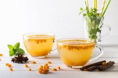 Thé sain d'argousier de vitamine dans des tasses en verre avec les baies d'argousier et les bâtons de cannelle crus frais, étoile Photos libres de droits
