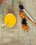 Thé sain d'argousier de Vitaminic dans la petite tasse avec les baies crues fraîches d'argousier et thé noir dans des cuillères e photos libres de droits