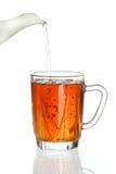 Thé se renversant dans la cuvette de thé transparente Photographie stock libre de droits
