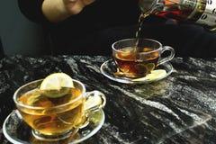 Thé se renversant de femme dans la tasse de thé à la table de marbre photographie stock