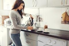 Thé se renversant de femme dans la tasse en céramique à la table images stock