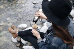 Thé se renversant de fille de voyageur de tasse de thermos, dehors Thé potable de jeune femme à la tasse Voyage de thème Femme ve photo stock