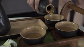 Thé se renversant de main femelle de bouilloire dans la cuvette tandis que cérémonie de thé de chinois traditionnel Femme ver banque de vidéos