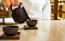 Thé se renversant femelle dans la tasse de thé en céramique photographie stock
