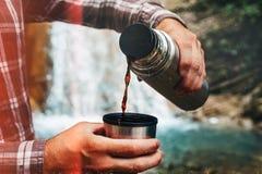 Thé se renversant ou café de voyageur méconnaissable à mettre en forme de tasse du thermos sur le fond de cascade Concept de tour image stock