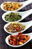 Thé sec assorti de santé de fines herbes dans des cuillères Photographie stock libre de droits