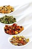 Thé sec assorti de santé de fines herbes dans des cuillères photos stock
