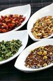 Thé sec assorti de santé de fines herbes dans des cuvettes images stock