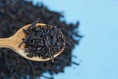 Thé sec noir dans une cuillère brune en bois Image stock