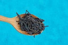 Thé sec noir dans une cuillère brune en bois sur un fond bleu Image libre de droits