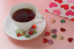 Thé, sucreries et serviettes avec des coeurs Image stock