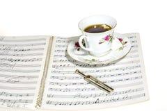 Thé sur un manuscrit de musique Images stock