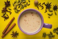 Thé traditionnel de lait avec des épices sur une table jaune Images libres de droits