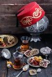 Thé turc avec les tasses en verre authentiques Deux tasses de thé turc et bonbons sur le fond en bois foncé Photos stock