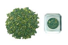 Thé vert à feuilles mobiles sur le fond blanc Image libre de droits