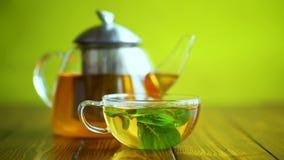 Thé vert chaud avec la menthe fraîche banque de vidéos