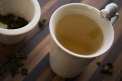 Thé vert dans la tasse de thé décorée sur la table en bois propre Photographie stock libre de droits