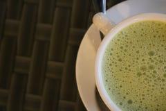 Thé vert dans une tasse sur la table image libre de droits