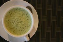 Thé vert dans une tasse sur la table avec la cuillère images stock