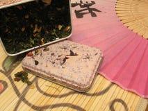 Thé vert de fruit dans l'étain et le ventilateur chinois Photos libres de droits
