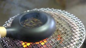Thé vert de torréfaction avec une moule de poterie de terre sur le brasero de terre de charbon de bois Le thé vert rôti est banque de vidéos