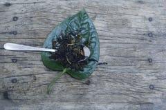Thé vert et cuillère abstraits avec la feuille sur le fond en bois photographie stock libre de droits