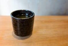 Thé vert japonais Matcha dans la tasse noire de poterie photo stock