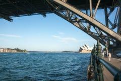 Théatre de l'opéra de Sydney le long des personnes du bord deux de port marchant sous le SI Photo libre de droits