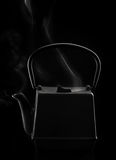 Théière asiatique de fer noir avec la vapeur Images stock