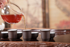 Théière, cuvettes et une sélection des thés rouges Image libre de droits