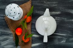 Théière et mandarines en céramique blanches avec les feuilles vertes sur la toile de jute sur un backgroundn en bois foncé Photos stock