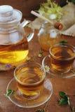 Théière et tasses de tisane et de pot de miel sur la table en bois Photo stock