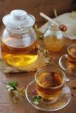 Théière et tasses de tisane sur la table en bois Photos stock