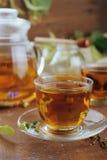 Théière et tasses de tisane sur la table en bois Images stock