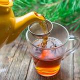 Théière jaune versant le thé noir dans la tasse en verre sur la table en bois photos libres de droits
