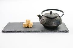 Théière noire de fonte et quatre cubes en sucre de canne à coté sur des rectums Photos stock