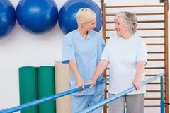 Thérapeute aidant la femme supérieure à marcher avec des barres parallèles photo libre de droits