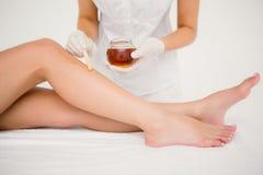 Thérapeute cirant la jambe de la femme au centre de station thermale image stock