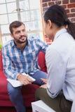 Thérapeute conseillant son patient de écoute Image libre de droits
