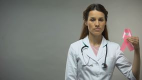 Thérapeute de femme avec le stéthoscope montrant le ruban rose, conscience de cancer du sein banque de vidéos