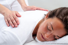 Thérapeute de Reiki faisant le traitement sur la femme Images stock