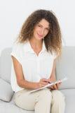 Thérapeute de sourire regardant l'appareil-photo prenant des notes photographie stock
