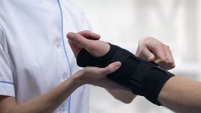 Thérapeute féminin appliquant l'accolade de poignet de titan au patient masculin, traitement de traumatisme clips vidéos