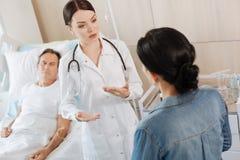 Thérapeute futé sérieux parlant à son épouse de patients Image stock
