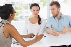 Thérapeute parlant avec des couples se reposant au bureau Photographie stock libre de droits