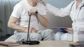 Thérapeute parlant avec le patient masculin supérieur à la maison, notant les disques médicaux images stock